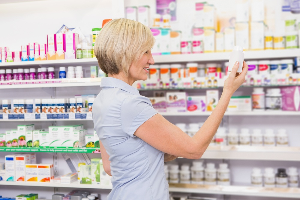 Pretty blonde customer looking at medicine in the pharmacy.jpeg