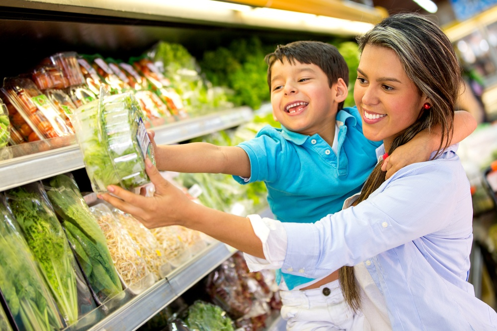 Woman at the supermarket with her son buying groceries.jpeg
