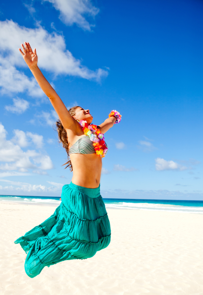 Happy Hawaiian woman at the beach jumping